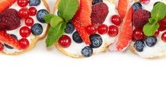 Profiteroles met bessenbes, aardbeien Stock Foto
