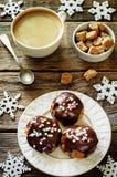 Profiteroles met chocoladesuikerglazuur en gekleurde poeder en koffie stock afbeeldingen