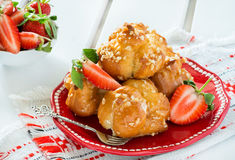 Profiteroles with nuts and strawberries Royalty Free Stock Photography