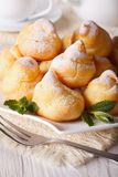 Profiteroles with powdered sugar close-up, vertical Royalty Free Stock Photography