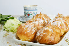 Profiteroles, rose and coffee Stock Images