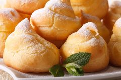 Profiteroles sprinkled with powdered sugar macro, horizontal Stock Image