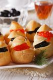Profiteroles stuffed with red and black caviar closeup. Vertical Stock Photos
