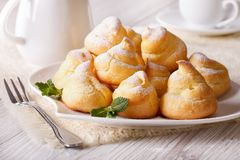 Profiteroles topped with powdered sugar, horizontal Stock Image