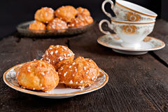 Profiteroles topped with sugar and vintage cup with tea on a dar Stock Image