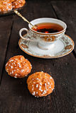Profiteroles topped with sugar and vintage cup with tea on a dar Royalty Free Stock Photo