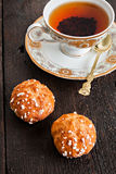 Profiteroles topped with sugar and vintage cup with tea on a dar Stock Photography