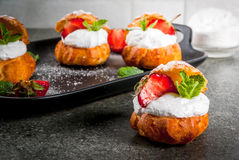 Profiteroles with whipped cream, strawberries and mint stock images