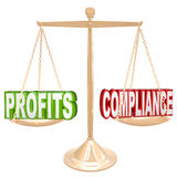 Profits and Compliance in Balance Scale Weighing Words. The words Profits and Compliance on a gold balance weighing the value of earning money and following Royalty Free Stock Photo