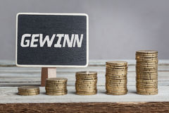 Profits in German language on sign. Gewinn profits in German language, white chalk type on black board, Euro money coin stacks of growth on wood table royalty free stock photography