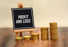 Profitti e perdite scritto sul bordo di gesso con la pila dorata di monete immagini stock libere da diritti
