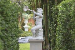 Profondément de la sculpture en cupidon dans le jardin photos libres de droits