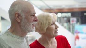 Profondità del campo poco profonda Fuoco sull'uomo senior Coppie senior felici che discendono in elevatore in centro commerciale stock footage