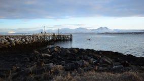 Profundamente abra el paisaje del fiordo con la cordillera nevosa poderosa en el fondo y el embarcadero viejo largo de la roca y  almacen de metraje de vídeo