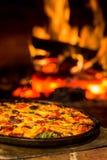 Profundidad baja de Oven Pizza de la pizza del campo con el fuego caliente foto de archivo libre de regalías