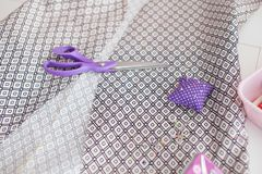 Profundidad del campo baja Materia textil o paño de costura Amortiguador del perno de las tijeras, y tela natural Tabla de trabaj imágenes de archivo libres de regalías