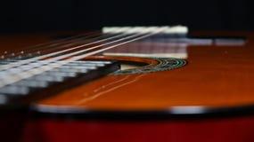 Profundidade da guitarra clássica de campo afiada que olha sobre a parte superior do corpo fotografia de stock royalty free