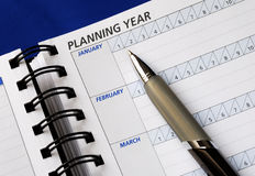 Progettando l'anno sul pianificatore di giorno Fotografia Stock