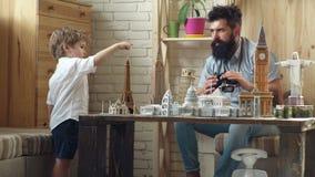 Progettazione del loro viaggio Ricerca dell'avventura Uomo e piccolo bambino con architettura binoculare e miniatura Figlio del r archivi video
