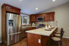 Progettazione della cucina di Brown con gli armadi da cucina di mogano fotografia stock