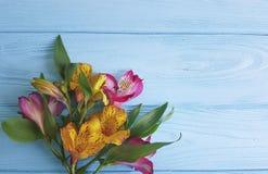Progettazione di Alstroemeria su un saluto di legno blu del fondo di compleanno Fotografie Stock Libere da Diritti