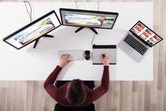 Progettazione di Making Web Page del progettista sul computer facendo uso della tavola del grafico fotografia stock