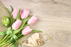 Progettazione di Pasqua con i tulipani, l'uovo ed il cuore di legno Fotografie Stock