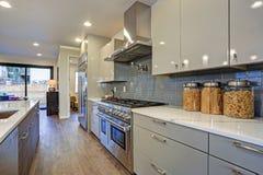 Progettazione moderna lucida della cucina con un'isola concentrare lunga immagine stock libera da diritti