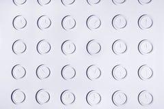 Progetti la parete bianca con gli orologi di parete non numerali rotondi identici di bianco Fondo di concetto di tempo Immagine Stock