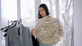 Progetti lo studio, indumenti di prova della donna adorabile sul gancio dal guardaroba in dell'interno luminoso stock footage