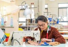 Progettista abbastanza femminile dell'abbigliamento dei giovani che fa lavoro Fotografia Stock