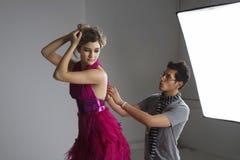 Progettista che regola vestito indietro del modello di moda in studio Fotografia Stock