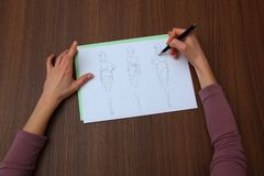 Progettista che valuta i disegni di modo Fotografia Stock