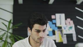 Progettista creativo facendo uso della tavola dei grafici mentre lavorando all'ufficio video d archivio