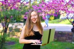 Progettista del paesaggio che utilizza computer portatile nel fondo di fioritura Fotografie Stock Libere da Diritti