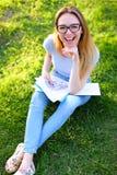 Progettista femminile del paesaggio che si siede sull'erba verde con i documenti in parco e che tiene soldi Fotografia Stock Libera da Diritti