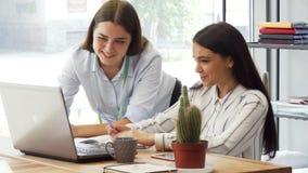 Progettista femminile e suo l'assistente che lavorano insieme sul computer portatile archivi video
