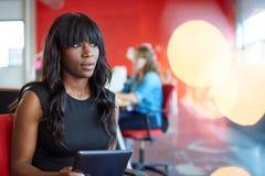 Progettista femminile sicuro che lavora ad una compressa digitale nello spazio ufficio creativo rosso Immagine Stock