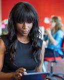 Progettista femminile sicuro che lavora ad una compressa digitale nello spazio ufficio creativo rosso Immagini Stock Libere da Diritti
