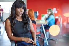 Progettista femminile sicuro che lavora ad una compressa digitale nello spazio ufficio creativo rosso Fotografie Stock