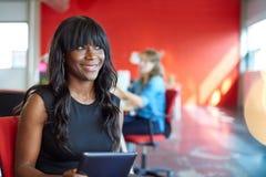 Progettista femminile sicuro che lavora ad una compressa digitale nello spazio ufficio creativo rosso Fotografie Stock Libere da Diritti