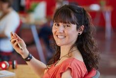 Progettista femminile sicuro che manda un sms su un telefono cellulare nello spazio ufficio creativo rosso Fotografia Stock