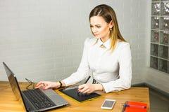 Progettista femminile in ufficio che lavora con la tavola ed il computer portatile del grafico digitale Retoucher di fotografia c Immagine Stock Libera da Diritti