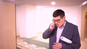 Progettista maschio attraente che tiene un disegno e che parla su un telefono cellulare archivi video