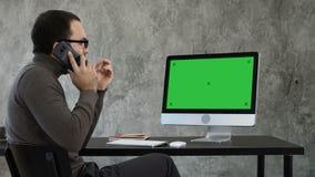 Progettista maschio che lavora al computer in ufficio contemporaneo Parla sul telefono e sul considerare che cosa è sullo schermo archivi video