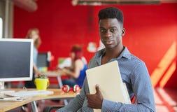 Progettista maschio sicuro che lavora e che esamina i documenti dentro una cartella nello spazio ufficio creativo rosso Immagine Stock