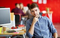 Progettista maschio sicuro che lavora nello spazio ufficio creativo rosso Immagini Stock Libere da Diritti