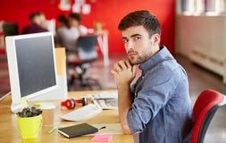 Progettista maschio sicuro che lavora nello spazio ufficio creativo rosso Fotografia Stock