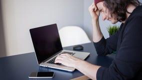 Progettista per un computer portatile, un posto di lavoro per le free lance Un giovane che si siede ad una tavola immagini stock
