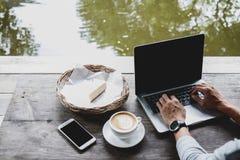 Progettista professionista di web che per mezzo del computer portatile con derisione sullo schermo per la c immagine stock